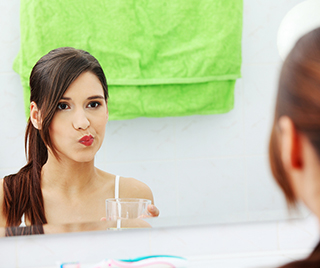 Woman rinsing with mouthwash.